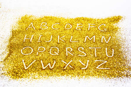 a composition with a capital letters of the alphabet on beautiful gold glitter. Background and texture of gold glitter. Luxury gold glitter sparkle shining texture background