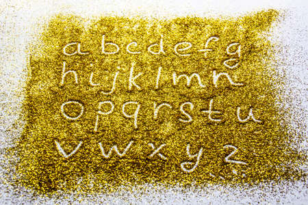 a composition with small letters of the alphabet on beautiful gold glitter. Background and texture of gold glitter. Luxury gold glitter sparkle shining texture background