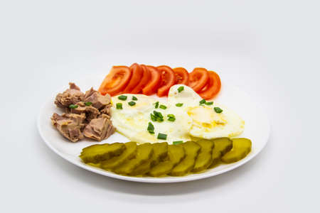 Delicious fresh tuna with eggs, tomatoes, cucmbers with green onion at the morning. Healthy and diet breakfast with tuna, eggs and vegetables on the white plate against white background