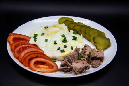 Delicious fresh tuna with eggs, tomatoes, cucmbers with green onion at the morning. Healthy and diet breakfast with tuna, eggs and vegetables on the white plate against dark background