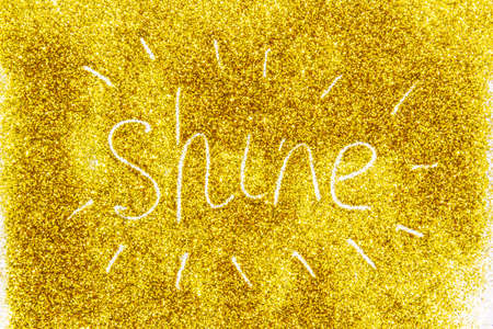 a composition with written a word shine on beautiful gold glitter. Background and texture of gold glitter. Luxury gold glitter sparkle shining texture background