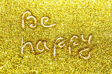a composition with written a words be happy on beautiful gold glitter. Background and texture of gold glitter. Luxury gold glitter sparkle shining texture background