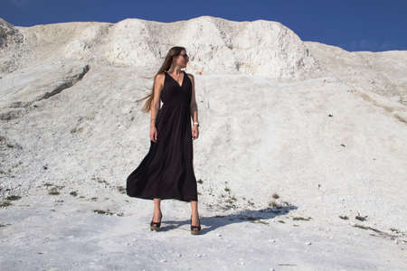 A beautiful girl in a black long dress stands against the background of chalk mountains.