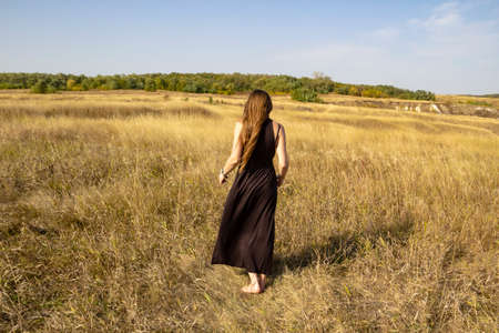 Pretty young dark haired woman in black dress stand in field. Beautiful girl outdoor in the field enjoy with freedom