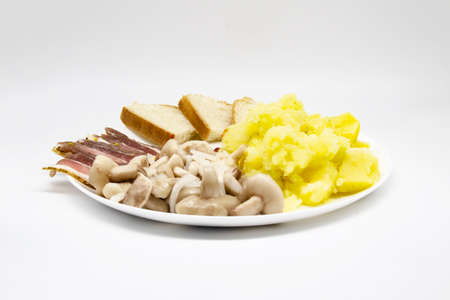 Pickled butter mushrooms with onions on a plate with bacon, potatoes and slices of bread isolated on  white