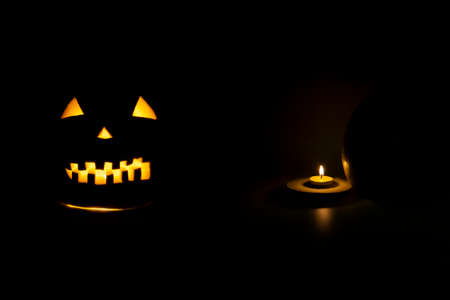 Helloween symbol with scary face behind a candel with fire
