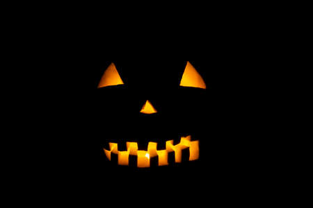 Helloween symbol with mad face, glowing eyes, mouth and teeth.