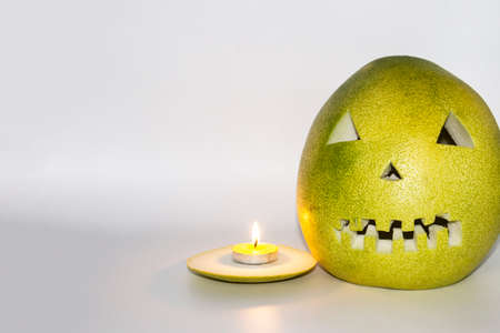 Scary face carved in pomelo fruit with candle in front isolated in gray background