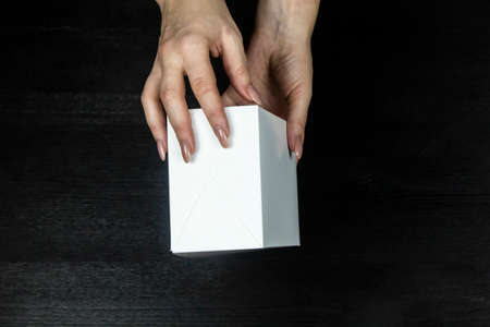 Female hands hold a white box on wood background