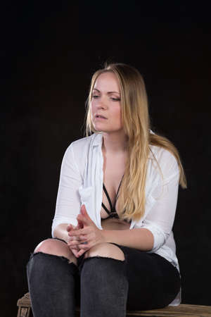 unsatisfied: Beautiful blond woman in her thirties in unbuttoned white shirt that reveals sexy underwear on a dark background at a photo studio.