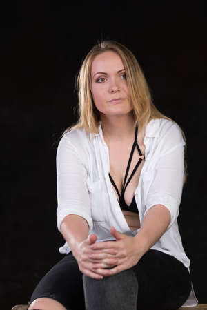 Beautiful blond woman in her thirties in unbuttoned white shirt that reveals sexy underwear on a dark background at a photo studio.