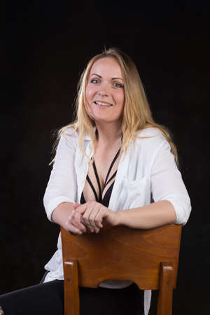 obligated: Beautiful blond woman in her thirties in unbuttoned white shirt that reveals sexy underwear on a dark background at a photo studio.