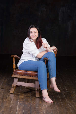 brown haired: Beautiful white brown haired female with colored in red ends, wearing mens white shirt and blue jeans, sitting in a vintage chair on a dark background.