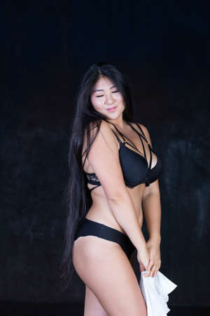 Stunningly beautiful curvy Asian girl with long gorgeous hair half dressed on a dark background in alluring, seductive and hot session.