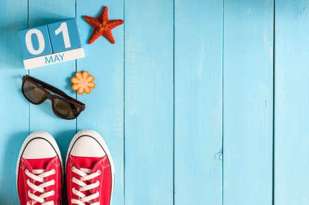 01 maja. Obraz 1 maja drewnianym kolorowym kalendarzu na niebieskim tle. dzień wiosny, puste miejsca na tekst. Międzynarodowy Dzień Pracowników.