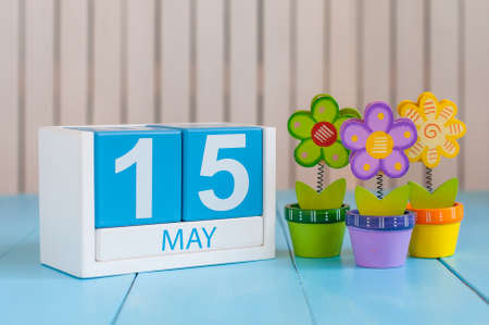 15th: May 15th. Image of may 15 wooden color calendar on white background with flowers. Spring day, empty space for text. World Remembrance Day Of AIDS Victims.