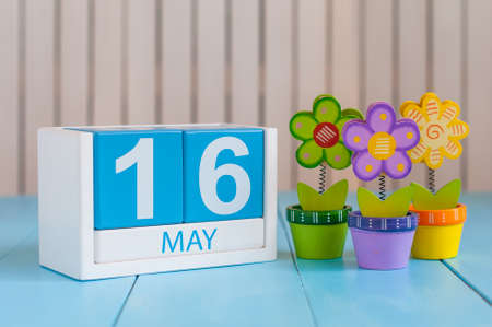 biographer: May 16th. Image of may 16 wooden color calendar on white background with flowers. Spring day, empty space for text.  Biographers Day.