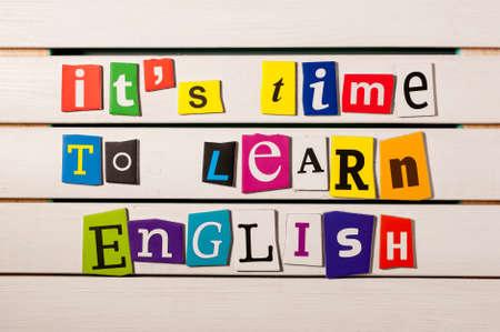 Concepto del aprendizaje Inglés. es el momento de aprender Inglés - escrito con recortes de letras revista en color sobre tabla de madera.