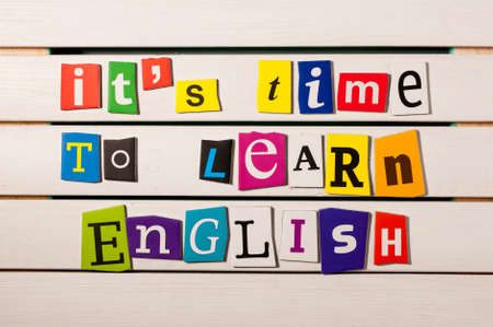 english letters: learning english concept. its time to learn English - written with color magazine letter clippings on wooden board.