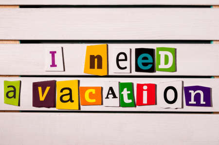 get tired: I need a vacation - written with color magazine letter clippings on wooden board. Vacation and travel, holiday concept.