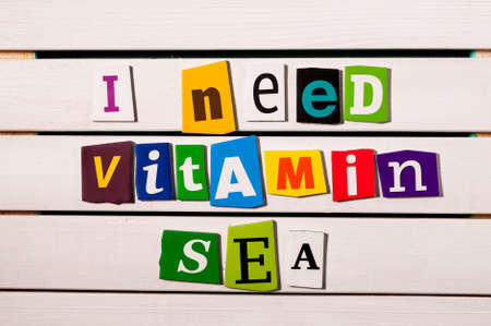 I need vitamin sea - written with color magazine letter clippings on wooden board. Summer vacation concept.