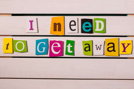 get away: I need get away - written with color magazine letter clippings on wooden board. Summer vacation concept.