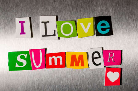 clippings: I Love Summer written with color magazine letter clippings on metal background. Concept of summer time and vacation.