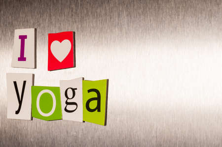 clippings: I Love Yoga written with color magazine letter clippings on metal background. Concept of sport and healthcare life.