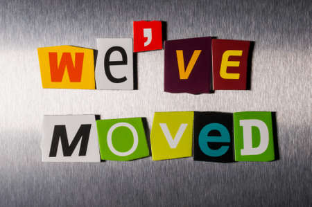 We've Moved written with color magazine letter clippings on metal background. Stock Photo