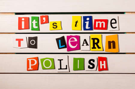 It's time to learn Polish - written with color magazine letter clippings on wooden board. Concept image.