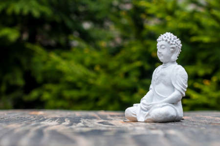 become: Sculpture of Buddha become enlightened on green background. Yoga and meditation concept.