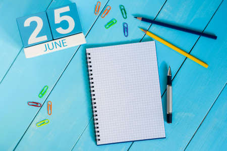 25th: June 25th. Image of june 25 wooden color calendar on blue background. Summer day. Empty space for text.