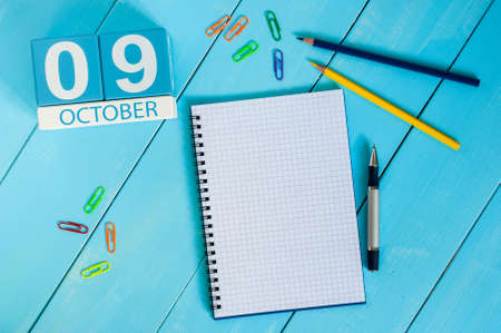 9th: October 9th. Image of October 9 wooden color calendar on blue background. Autumn day. Empty space for text.