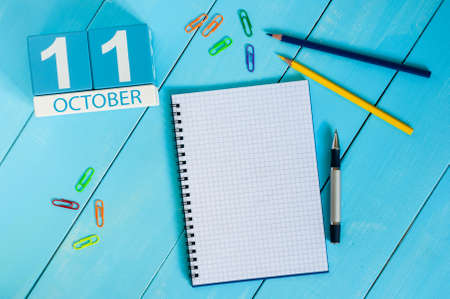 11th: October 11th. Image of October 11 wooden color calendar on blue background. Autumn day. Empty space for text. Stock Photo