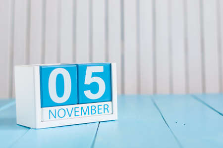 5th: November 5th. Image of november 5 wooden color calendar on blue background. Autumn day. Empty space for text.