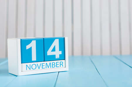 14th: November 14th. Image of november 14 wooden color calendar on blue background. Autumn day. Empty space for text.