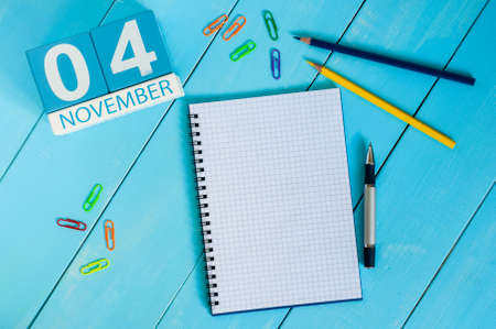 test deadline: November 4th. Image of november 4 wooden color calendar on blue background. Autumn day. Empty space for text.