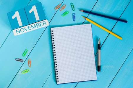 11th: November 11th. Image of november 11 wooden color calendar on blue background. Autumn day. Empty space for text.