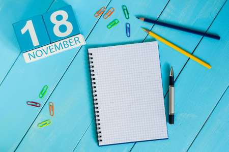 the eighteenth: November 18th. Image of november 18 wooden color calendar on blue background. Autumn day. Empty space for text.