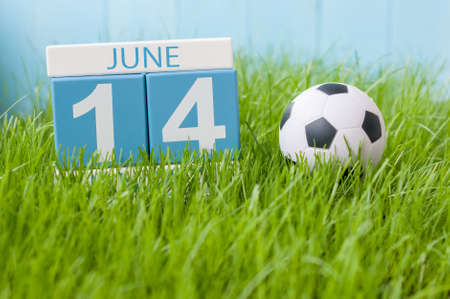 14th: June 14th. Image of june 14 wooden color calendar on green grass background with football outfit. Summer day.