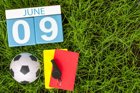 9th: June 9th. Image of june 9 wooden color calendar on green grass background with football outfit. Summer day. Stock Photo