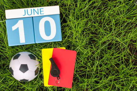 10th: June 10th. Image of june 10 wooden color calendar on green grass background with football outfit. Summer day. Stock Photo