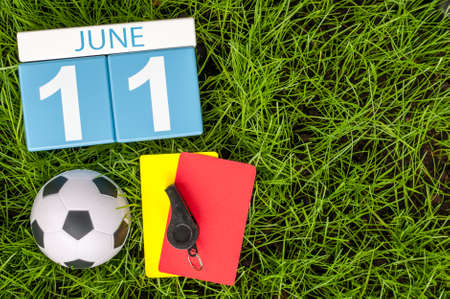 11th: June 11th. Image of june 11 wooden color calendar on green grass background with football outfit. Summer day.