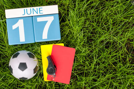 17th: June 17th. Image of june 17 wooden color calendar on green grass background with football outfit. Summer day.