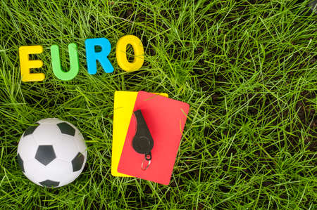 fair play: Euro football championship - image with ball, referee yellow, red card on green lawn. Symbol of soccer and fair play. Empty space for text.