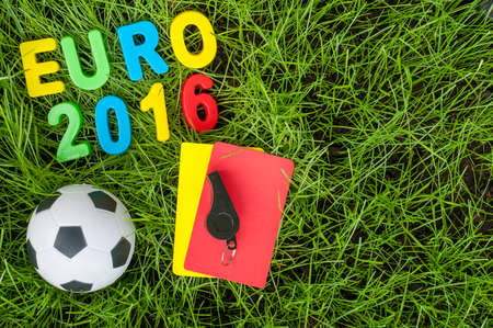 fair play: Euro 2016 football championship - image with ball, referee yellow, red card on green lawn. Symbol of soccer and fair play. Empty space for text.