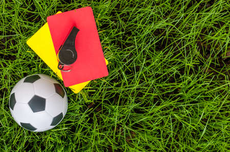arbitrator: Soccer referee outfit a yellow and red card with ball on lawn of stadium. Football background. Stock Photo