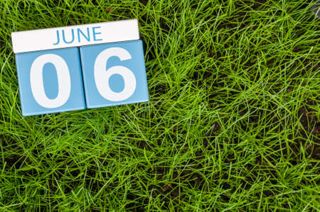 greengrass: June 6th. Image of june 6 wooden color calendar on greengrass lawn background. Summer day, empty space for text.