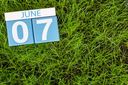 greengrass: June 7th. Image of june 7 wooden color calendar on greengrass lawn background. Summer day, empty space for text.