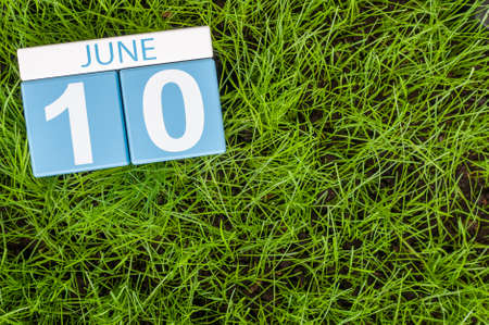 10th: June 10th. Image of june 10 wooden color calendar on greengrass lawn background. Summer day, empty space for text. Stock Photo